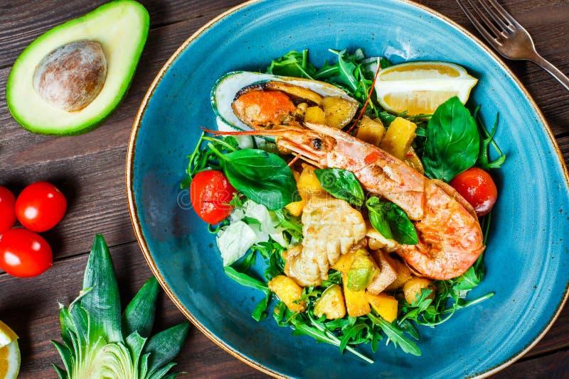 Warmer Salat mit Meeresfrüchten, Langoustine, Miesmuscheln, Garnelen, Kalmar, Kammmuscheln, Mango, Ananas, Avocado lizenzfreie stockbilder