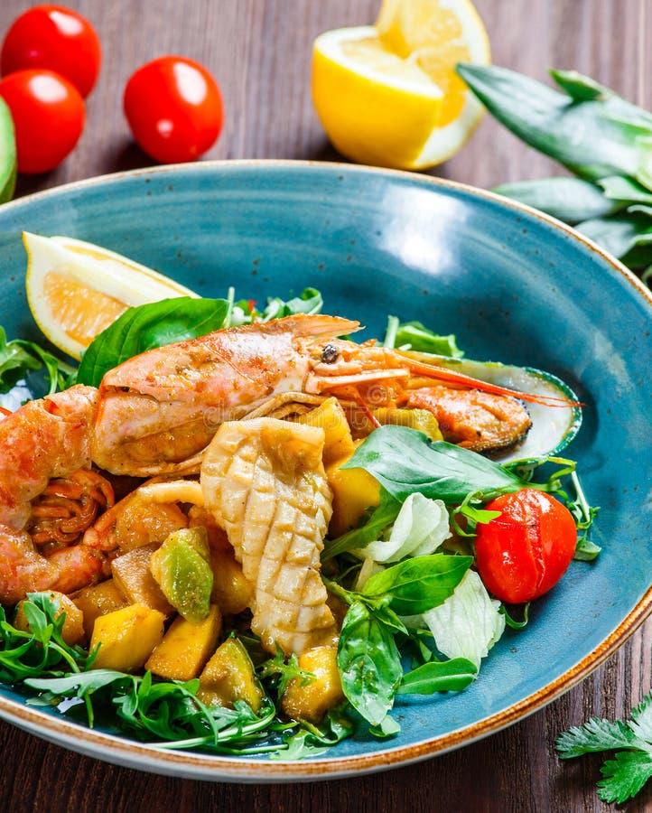 Warmer Salat mit Meeresfrüchten, Langoustine, Miesmuscheln, Garnelen, Kalmar, Kammmuscheln, Mango, Ananas, Avocado stockbilder