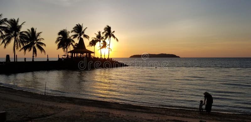 Warmer Sonnenuntergang, Küste, Mutter und Tochter spielen Wasser, Schatten, goldenes Meer stockfotos