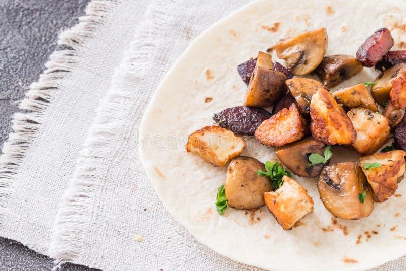 Warmer Taco mit gegrillten Pilzen, spanische würzige Wurstchorizo, mexikanische Tortillas, zypriotisches Käse halloumi stockfotos