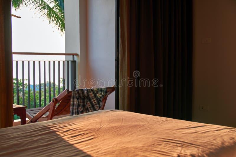 Warmer tropischer Abend des Konzeptes im Hotelzimmer auf dem Strand Sonniges Abendlicht belichtet das Bett durch die offene Tür lizenzfreie stockfotos