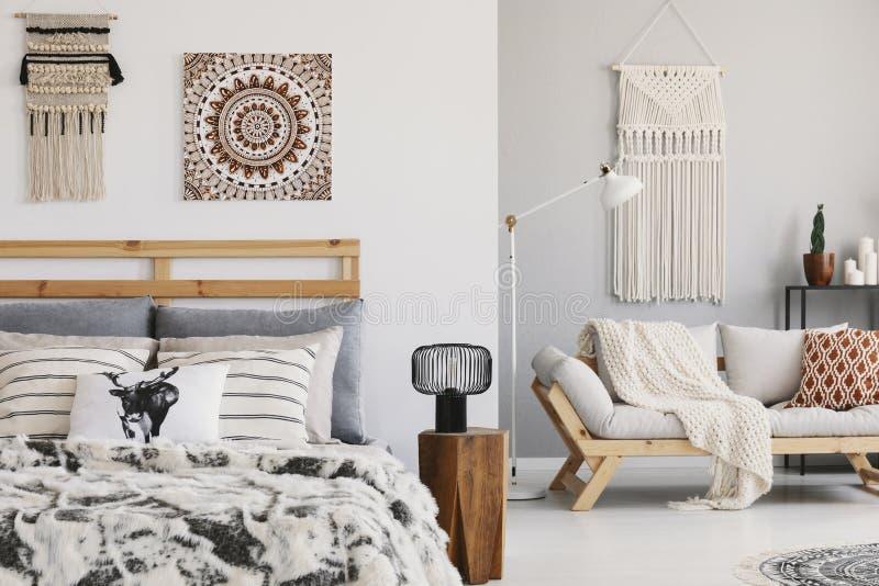 Warmes ethno Schlafzimmer mit kopierten Kissen auf dem Bett und der Couch und Makramee auf der Wand stockfoto