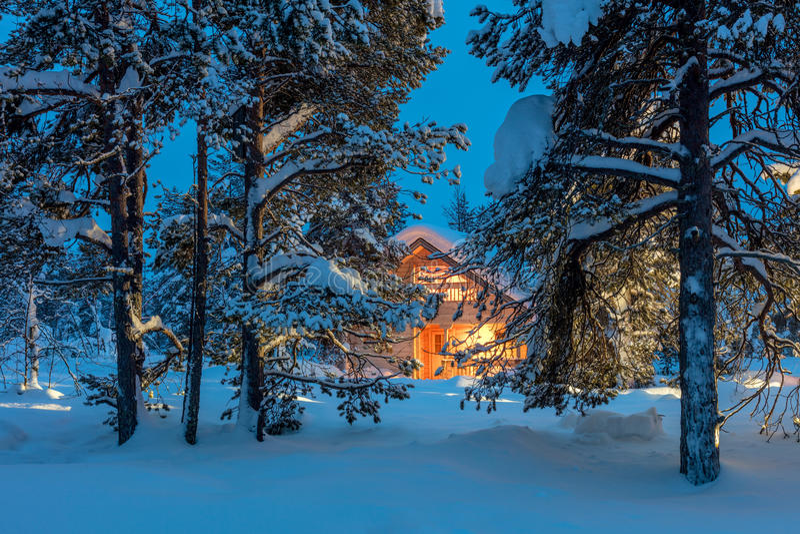 Warmes Haus im schneebedeckten Nachtwinterwald stockbilder