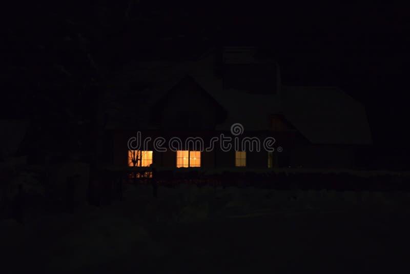 Warmes Licht durch süßes Haus des Fensters zu Hause nachts, Weihnachtsambiente lizenzfreie stockbilder