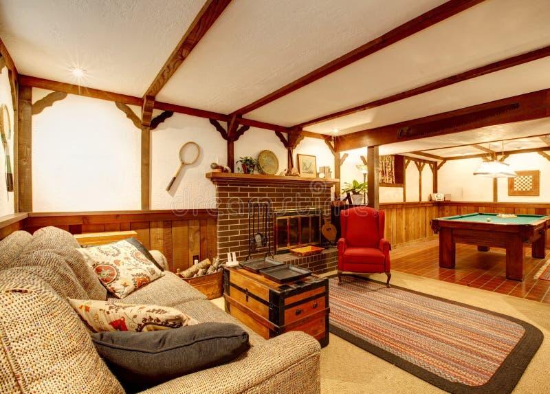 Warmes rustikales versorgtes Wohnzimmer mit einem Kamin und Pool tabl lizenzfreie stockbilder