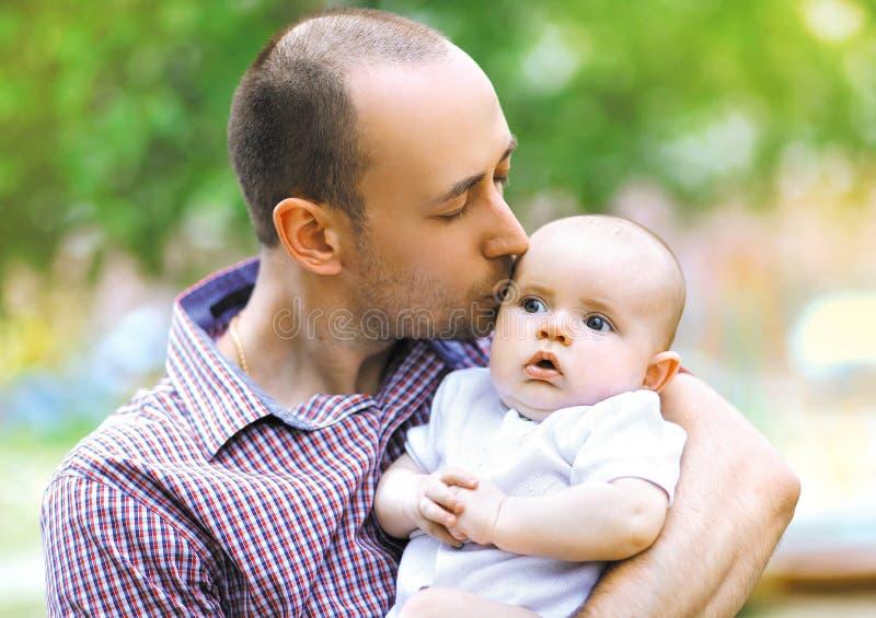 Warmes, sinnliches Foto, Vater küsst kleines Baby stockfotos