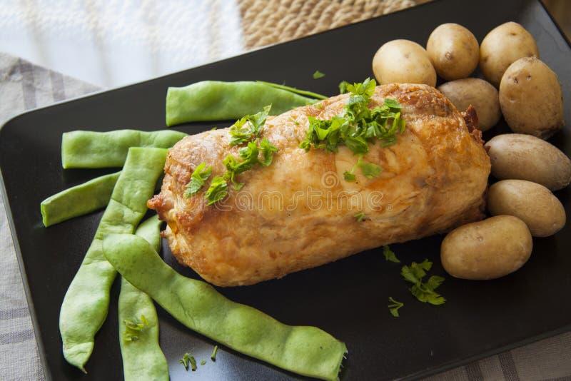 Warmhoudplaat van gevuld avondmaal: kippenbroodje met aardappel en bonen royalty-vrije stock afbeelding