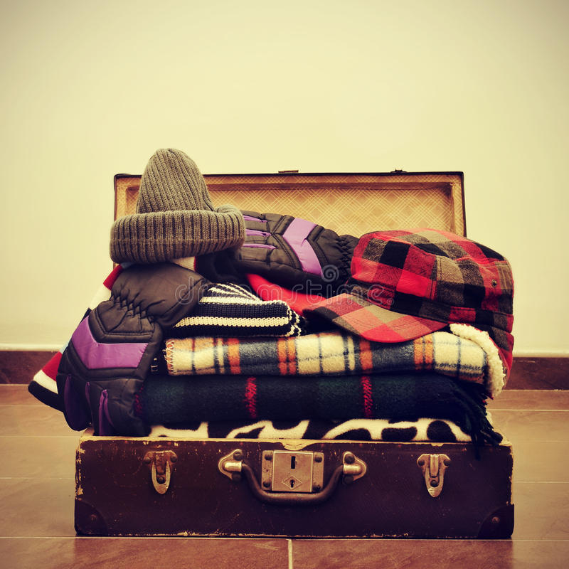 Warming clothes in a suitcase. A pile of warming clothes, such as gloves, caps or blankets, in an old suitcase, with a retro effect royalty free stock images