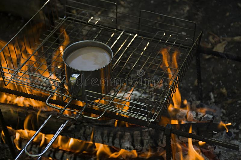 Warming a cup of coffee while burning a fire in a wild campsite royalty free stock image