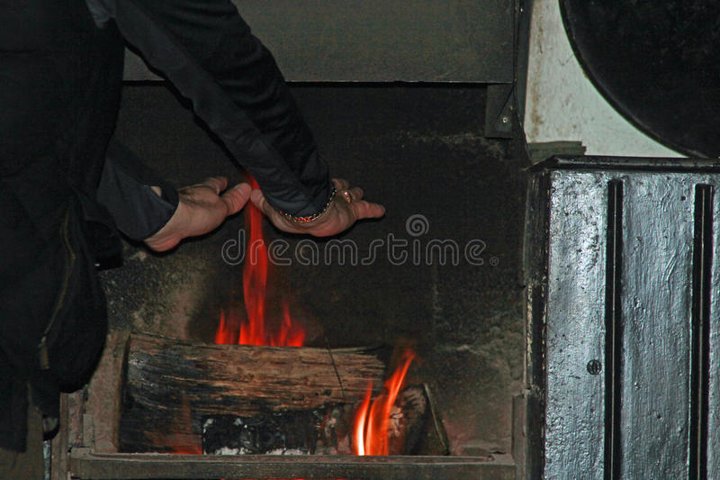 Warming hands on a log fire. Man warming his hands on a open fire with roaring logs wooden fire surround symbolizing heating, warmth, Winter and the desire for stock photos