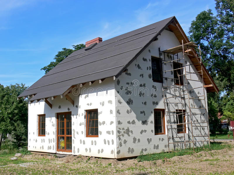 Warming isolation. Small house covered warming isolation and scaffolding royalty free stock photography