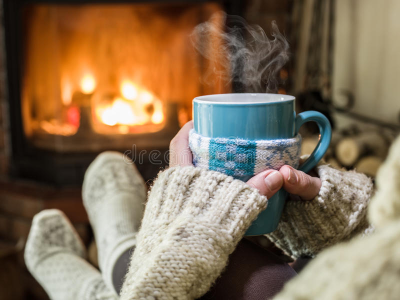 Warming and relaxing near fireplace. Warming and relaxing near fireplace with a cup of hot drink stock photo