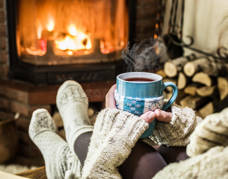 Warming and relaxing near fireplace. Warming and relaxing near fireplace with a cup of hot drink royalty free stock image
