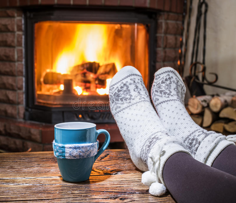 Warming and relaxing near fireplace with a cup of hot drink. Warming and relaxing near fireplace. Woman feet near the cup of hot drink in front of fire stock images