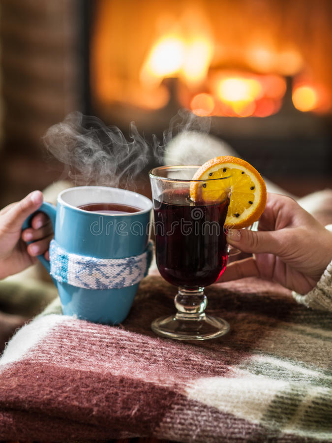 Warming and relaxing near fireplace with a cup of hot drink. Warming and relaxing near fireplace. Woman feet near the cup of hot drink in front of fire stock photo
