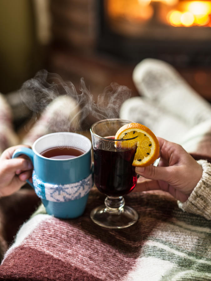Warming and relaxing near fireplace with a cup of hot drink. Warming and relaxing near fireplace. Woman feet near the cup of hot drink in front of fire royalty free stock photos