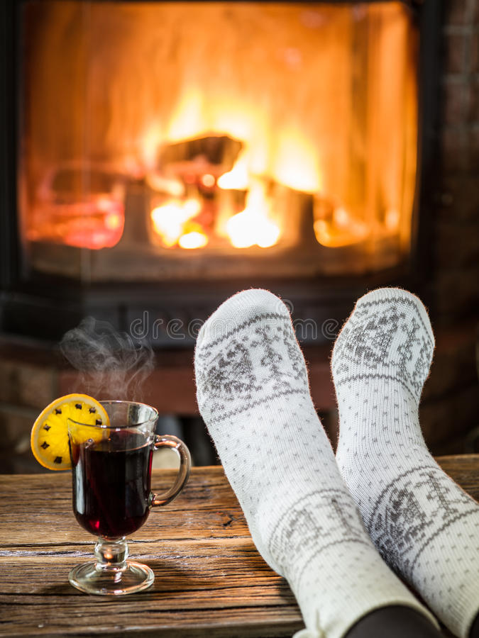 Warming and relaxing near fireplace with a cup of hot wine. Warming and relaxing near fireplace. Woman feet near the cup of hot wine in front of fire royalty free stock photo