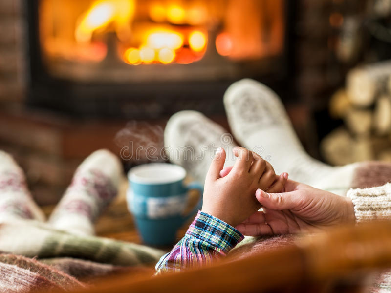 Warming and relaxing near fireplace. Mother and daughter holding hands in front of fire stock images