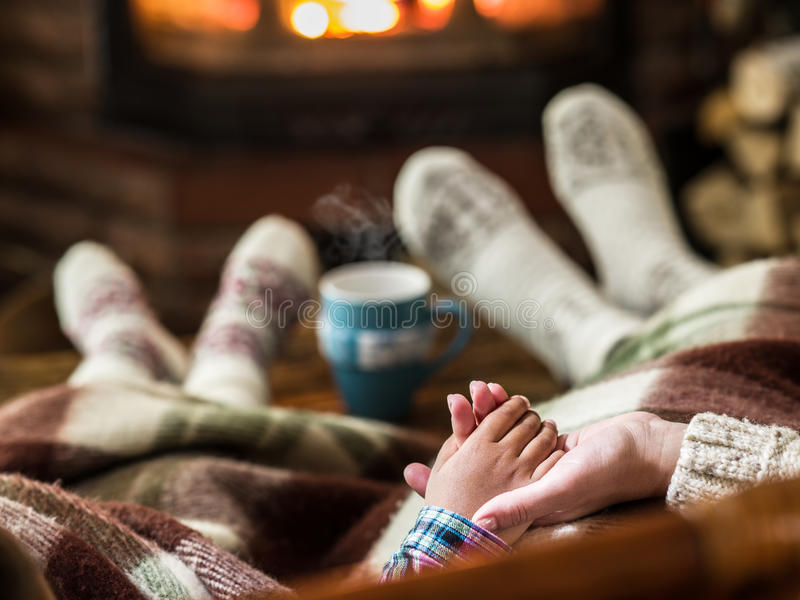 Warming and relaxing near fireplace. Mother and daughter holding hands in front of fire royalty free stock photography