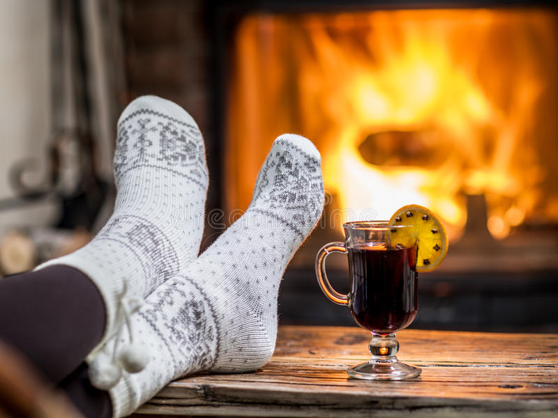 Warming and relaxing near fireplace. Woman feet near the cup of hot wine in front of fire royalty free stock photography
