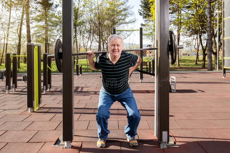 Warming up in the fitness park. Elderly man warming up at the weights bar in the fitness park outdoors gym royalty free stock photo