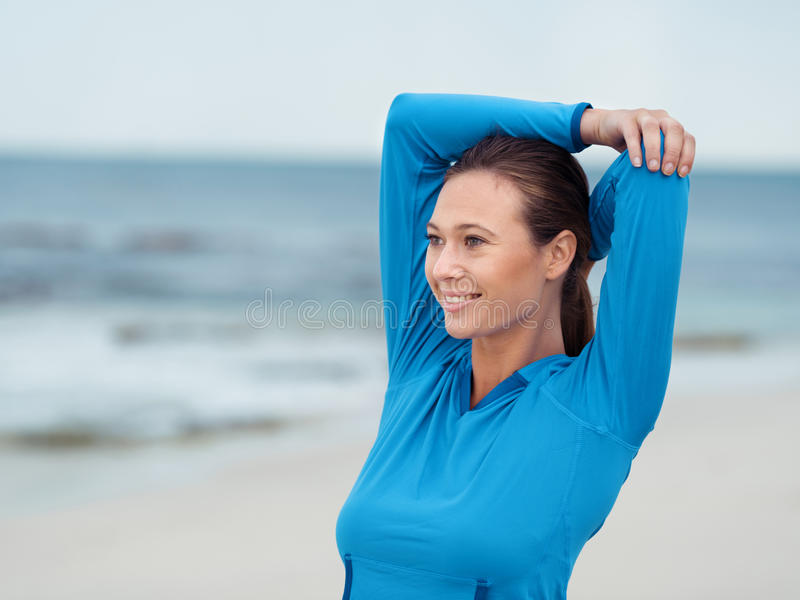 Warming up before a good run. Sporty young woman stretching on the sea coast royalty free stock photos