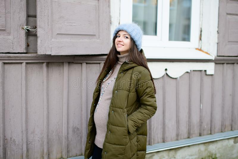 Warmly dressed pregnant girl Beautiful pregnant woman dressed in gray knitted sweaters, hat, scarf and jeans, holding pink cups. With hot tea and walking royalty free stock photography