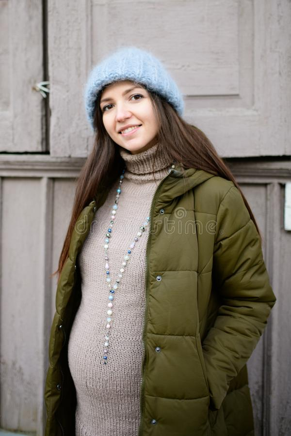 Warmly dressed pregnant girl Beautiful pregnant woman dressed in gray knitted sweaters, hat, scarf and jeans, holding pink cups. With hot tea and walking stock image