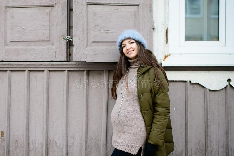 Warmly dressed pregnant girl Beautiful pregnant woman dressed in gray knitted sweaters, hat, scarf and jeans, holding pink cups. With hot tea and walking royalty free stock image