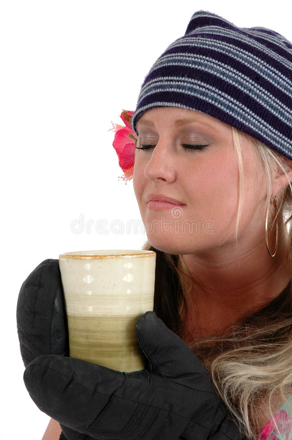 Warmth. A woman in a ski hat and mittens drinking a cup of hot coffee or cocoa stock images