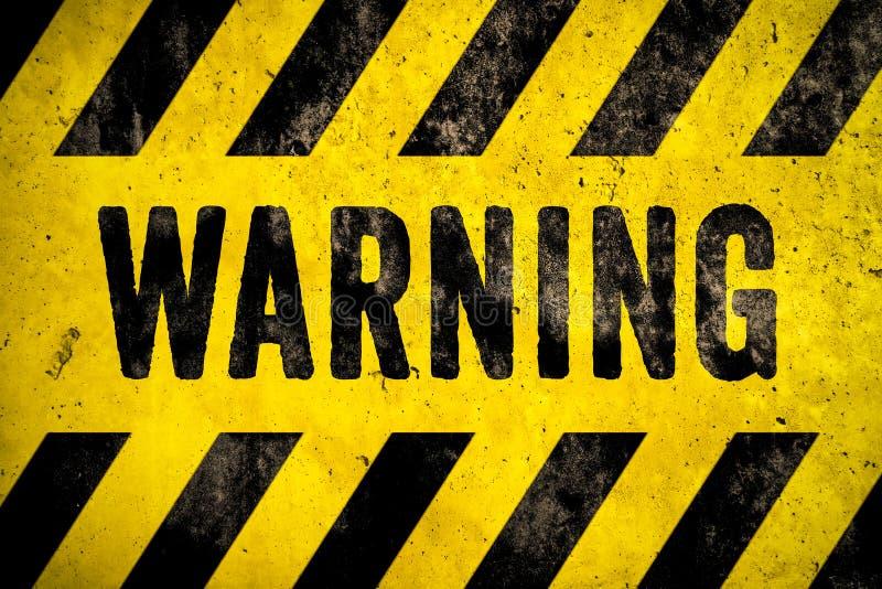 WARNENDER Warnschildworttext als Schablone mit den gelben und schwarzen Streifen gemalt über Betonmauerzement-Beschaffenheitshint stockfotografie