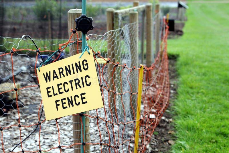 Warnendes elektrisches Zaunzeichen auf elektrischem Zaun stockfotos