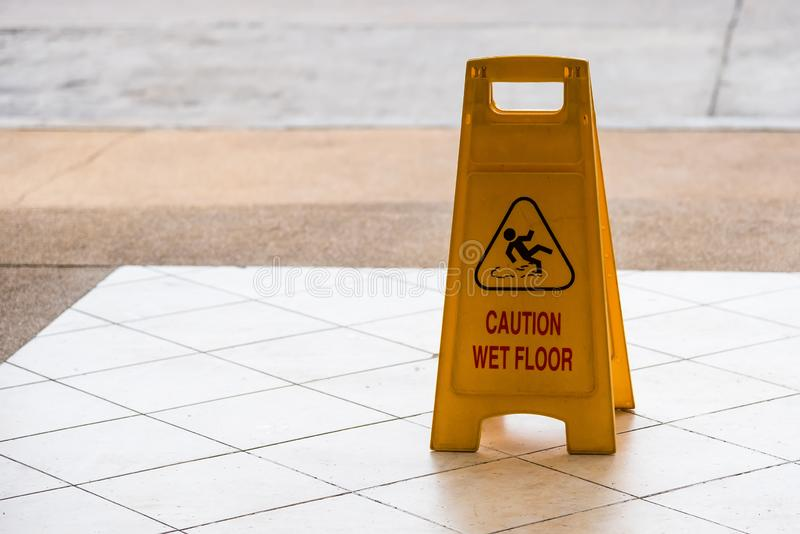 Warning beware accident concept, The image of yellow caution wet floor plastic sign put on the concrete floor. Symbol, notice, interior, precaution, fall royalty free stock photos