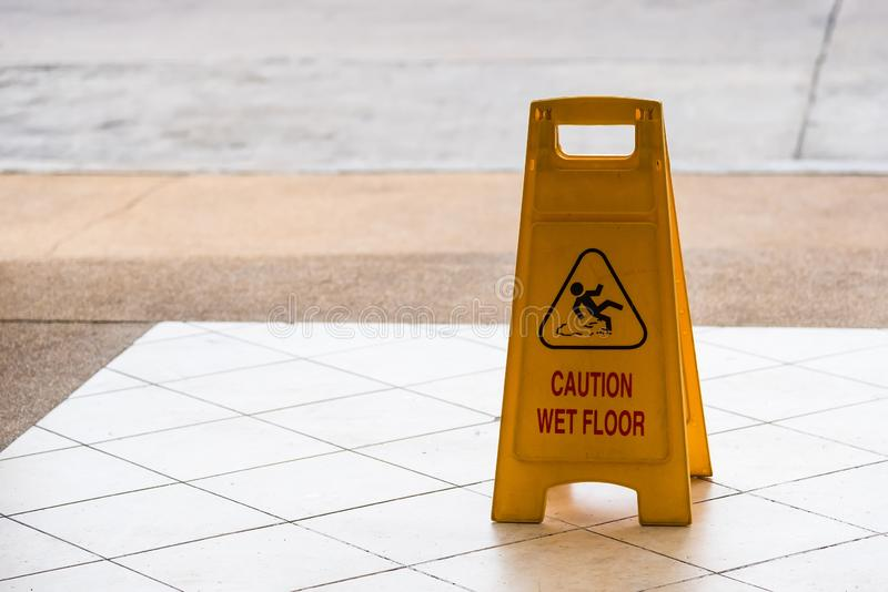 Warning beware accident concept, The image of yellow caution wet floor plastic sign put on the concrete floor. Symbol, notice, interior, precaution, fall royalty free stock image