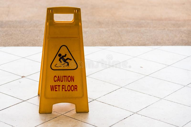 Warning beware accident concept, The image of yellow caution wet floor plastic sign put on the concrete floor. Symbol, notice, interior, precaution, fall stock photography