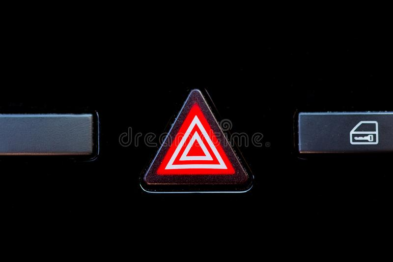 Warning button illuminated on the dashboard of a car stock photography