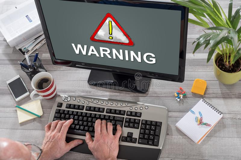 Warning concept on a computer. Man using a computer with warning concept on the screen stock photography