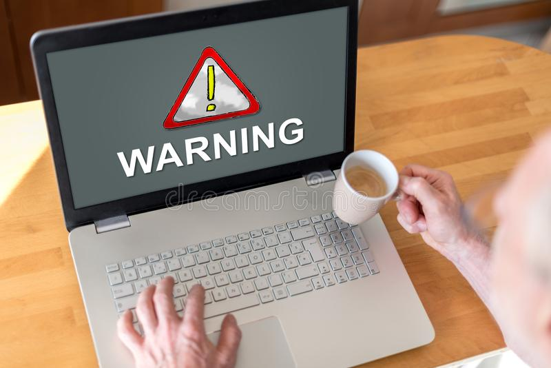 Warning concept on a laptop. Man using a laptop with warning concept on the screen royalty free stock photography