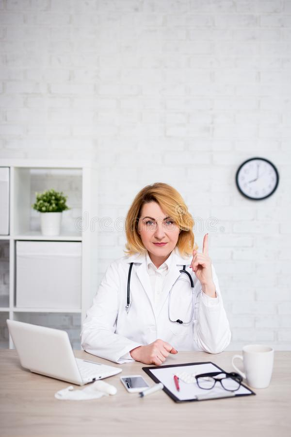 Warning concept - serious mature female doctor showing attention sign in office - copy space over white wall. Warning concept - serious mature female doctor royalty free stock photos