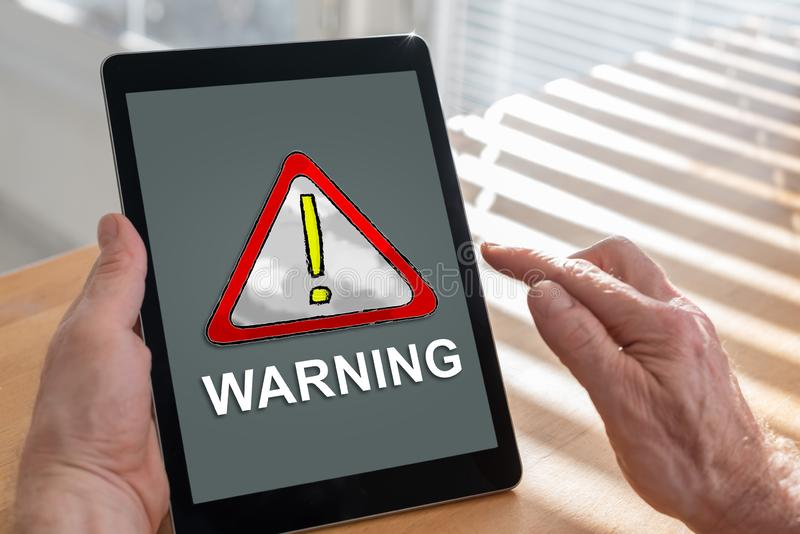 Warning concept on a tablet. Tablet screen displaying a warning concept royalty free stock photos