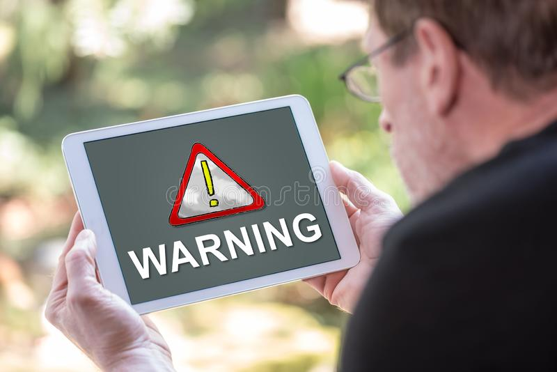 Warning concept on a tablet. Tablet screen displaying a warning concept royalty free stock photography