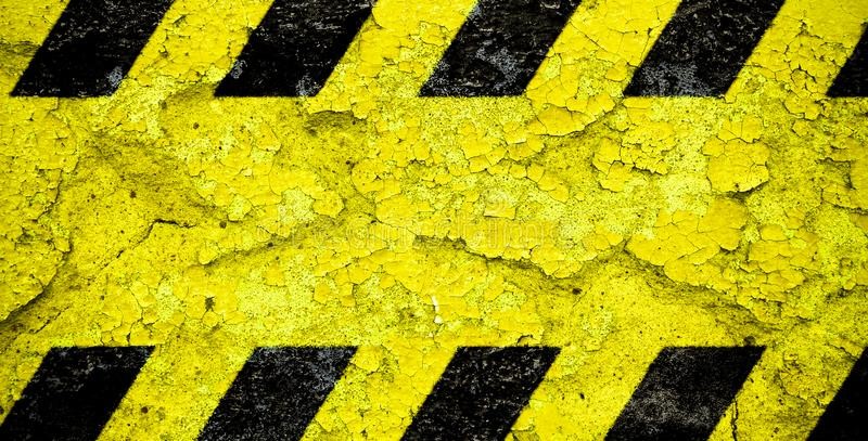 Warning danger sign yellow and black stripes pattern with yellow area over concrete cement wall facade peeling cracked paint royalty free stock image
