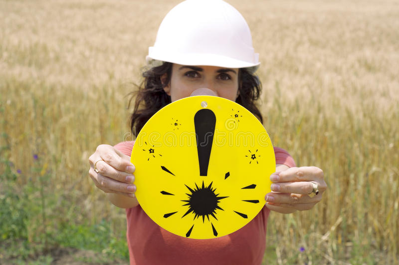 Warning: Protection equipment needed. Woman holding the exclamation mark indicating that you need protection equipment royalty free stock image