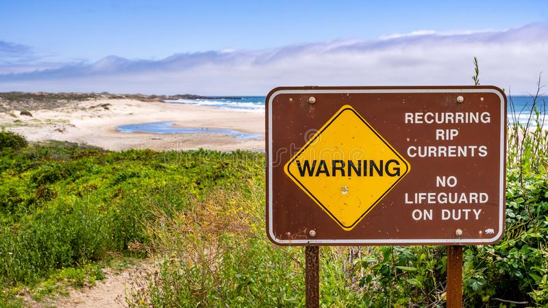 Warning regarding recurring rip currents and no lifeguard on duty posted on the Pacific Ocean coastline, California royalty free stock photography