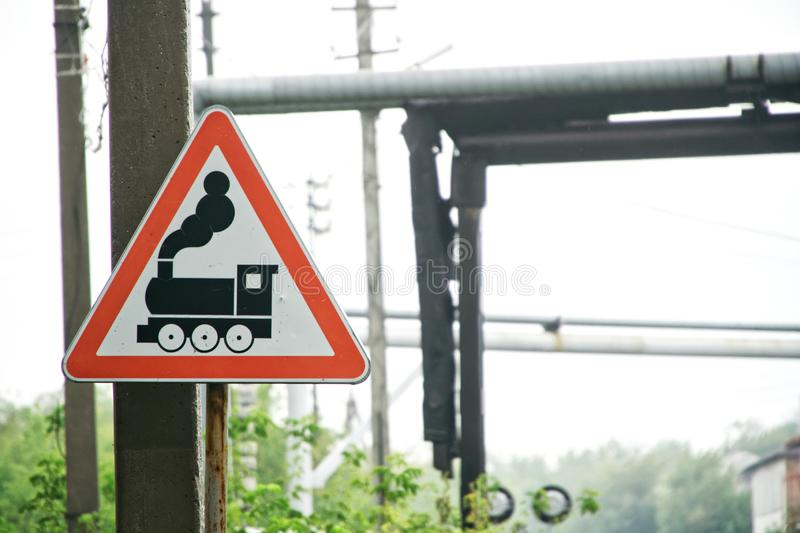 Warning road sign Caution train in the industrial area. Railroad crossing. Against the background of the pipeline stock image