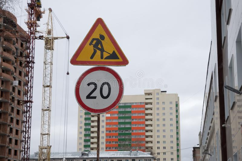 Warning road sign - repair work and speed limit sign on the background of an apartment building. royalty free stock image