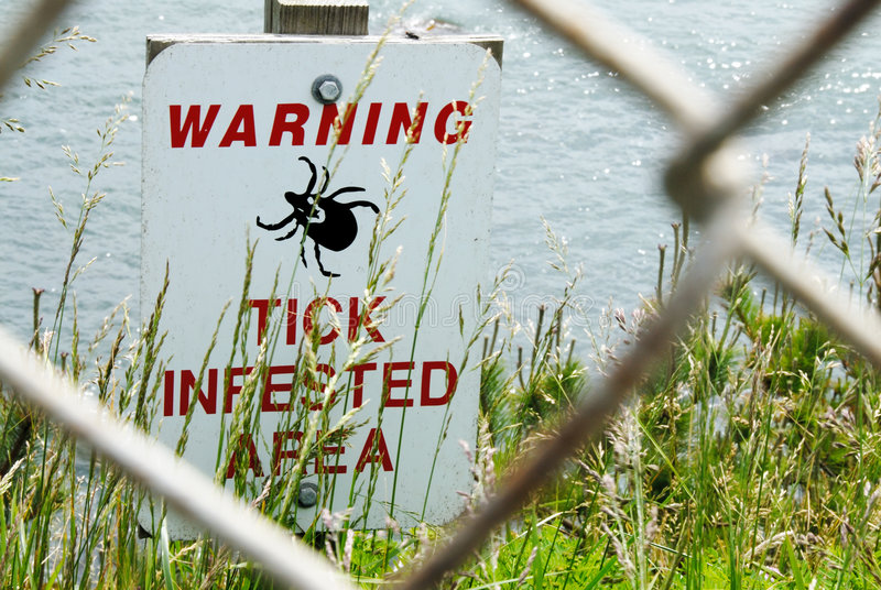 Warning Sign. A sign warning about ticks. Some ticks are known to carry a bacteria that causes Lyme disease stock photography