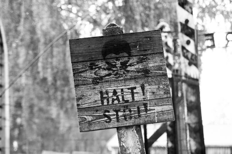Warning sign on the barbed wire in a concentration camp in Auschwitz (Poland) royalty free stock photo