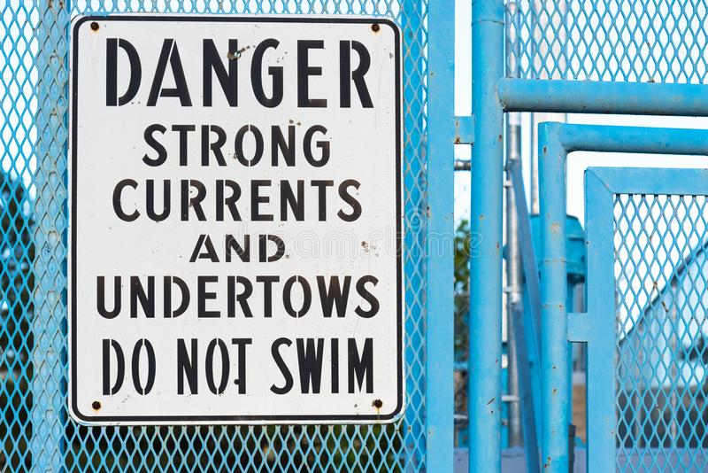 Do not swim sign warning of strong currents and undertows. Warning sign on blue metal fence telling people not to swim in river due to strong currents and stock image