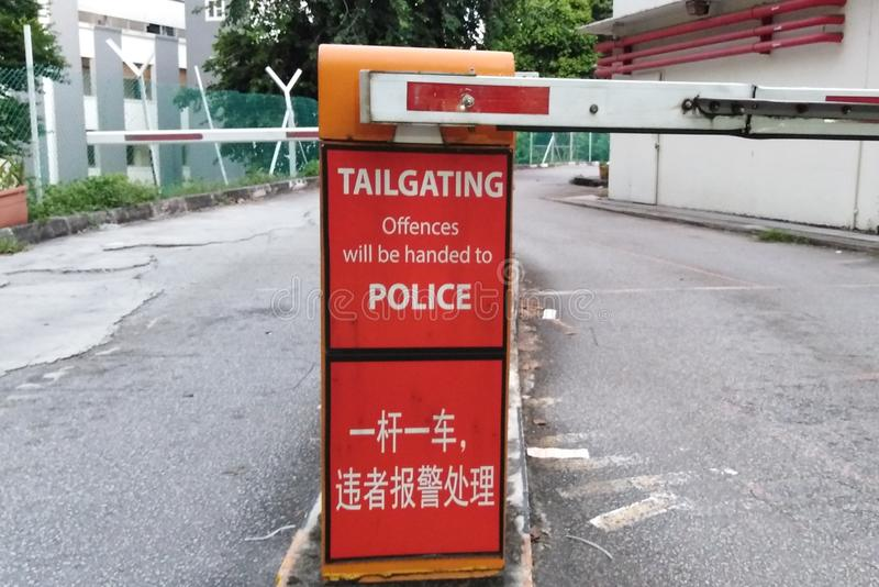 Warning sign at carpark. A warning sign at a carpark about tailgating police singapore law signpost notice english chinese words language official offences stock photos